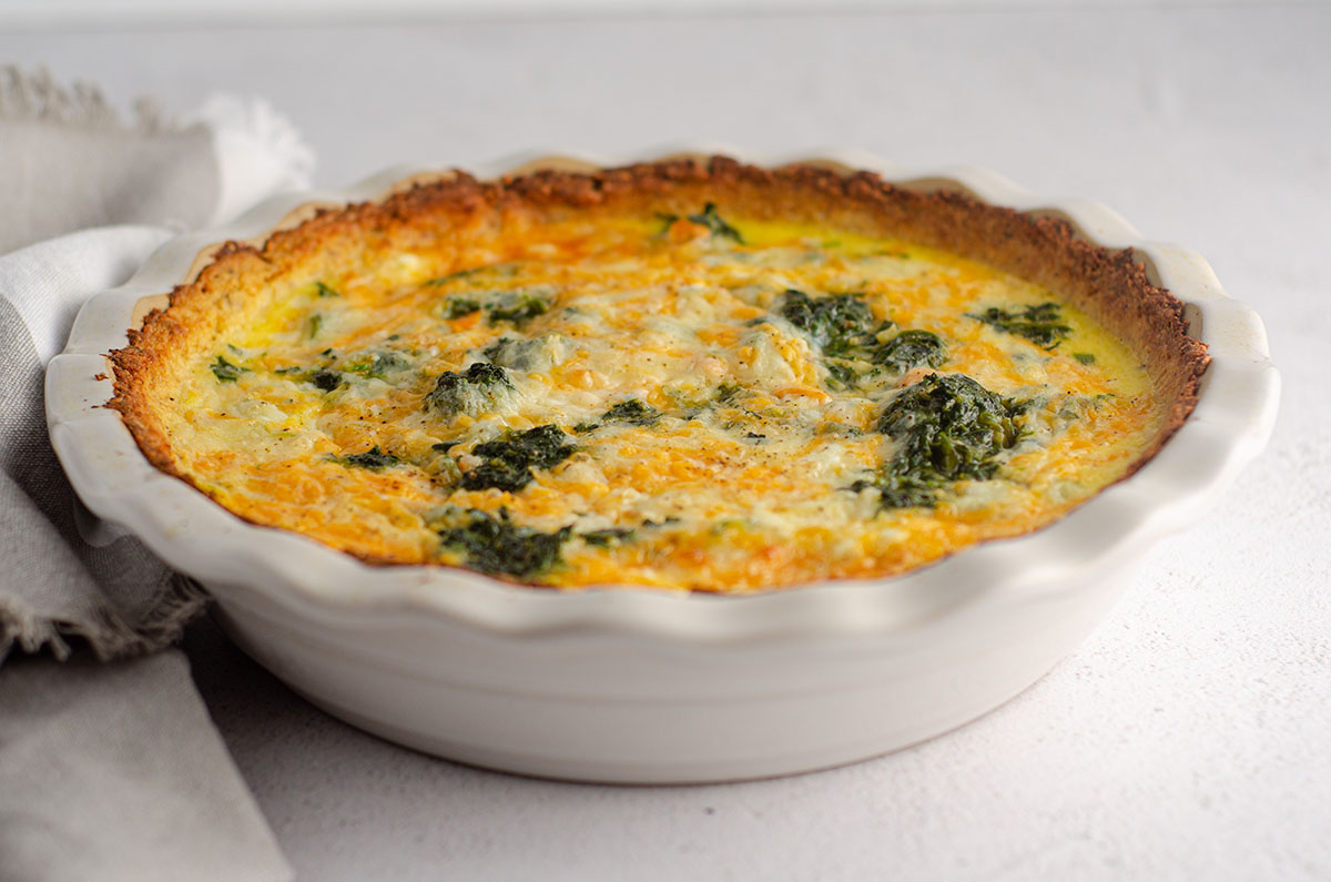 cheesy vegetable quiche with cauliflower crust in a pie plate