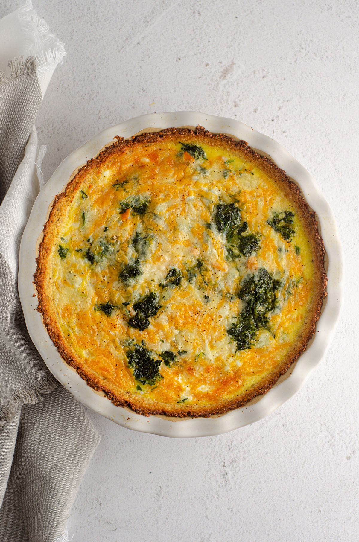 aerial photo of cheesy vegetable quiche with cauliflower crust in a pie plate