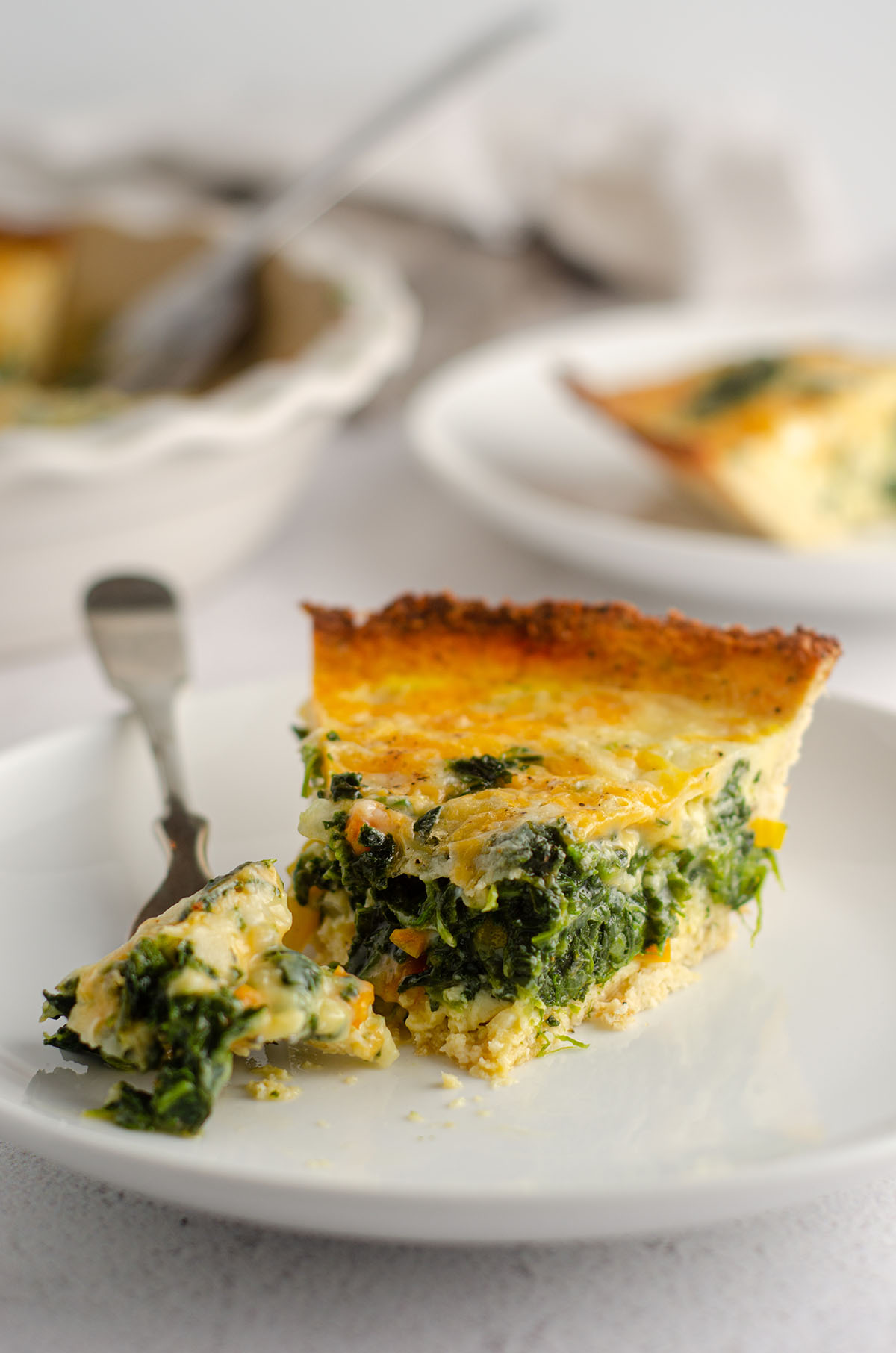 slice of cheesy vegetable quiche with cauliflower crust sitting on a plate
