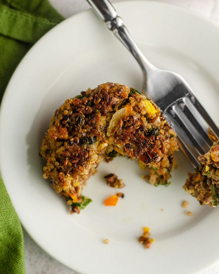 quinoa patty sitting on a plate with a bite taken out