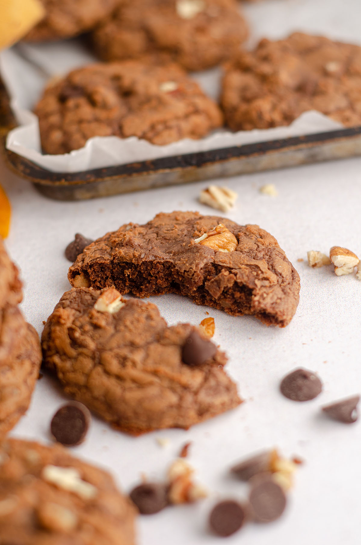 a brownie cookie broken in half with chocolate chips and nuts scattered around it