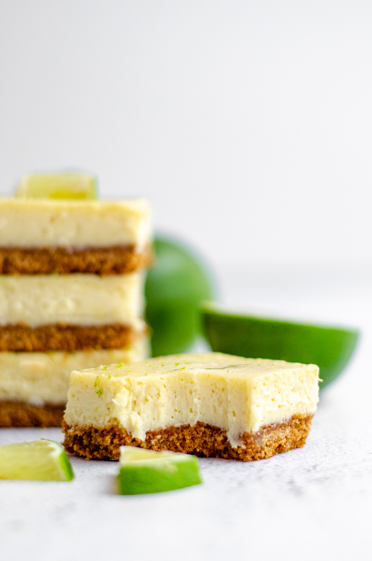 a key lime pie bar in the foreground with a bite taken out of it and a stack of key lime pie bars in the background