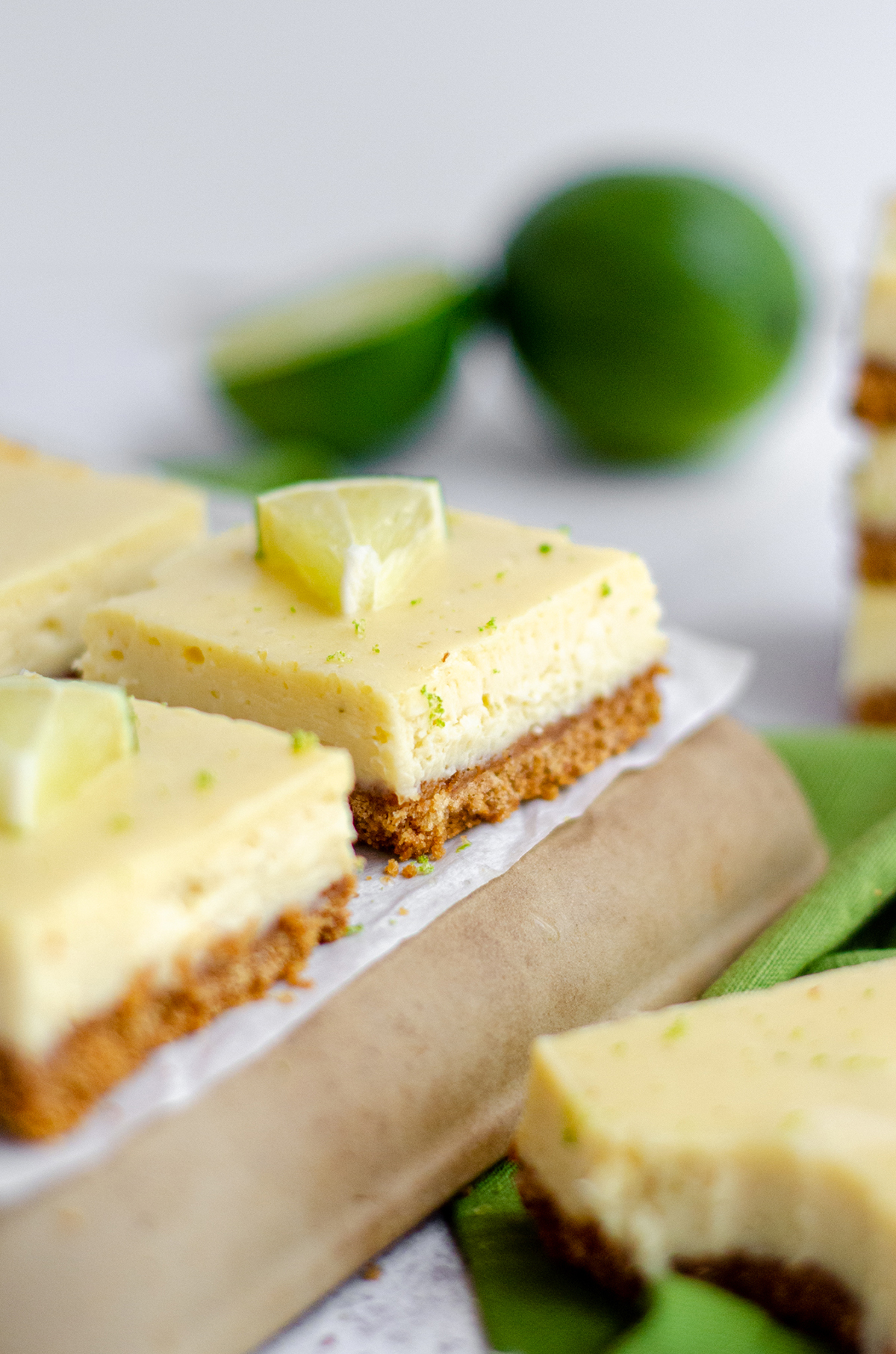 key lime pie bars on a platter with limes and slices of limes scattered around them