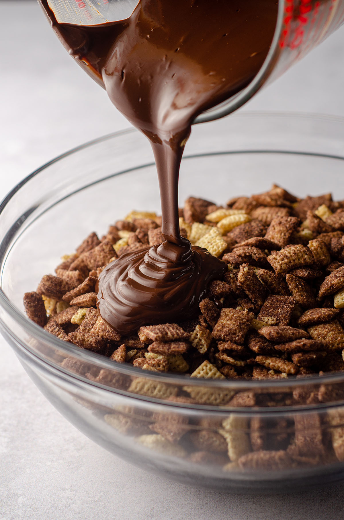 melted chocolate being poured onto chocolate chex cereal to make brownie batter puppy chow