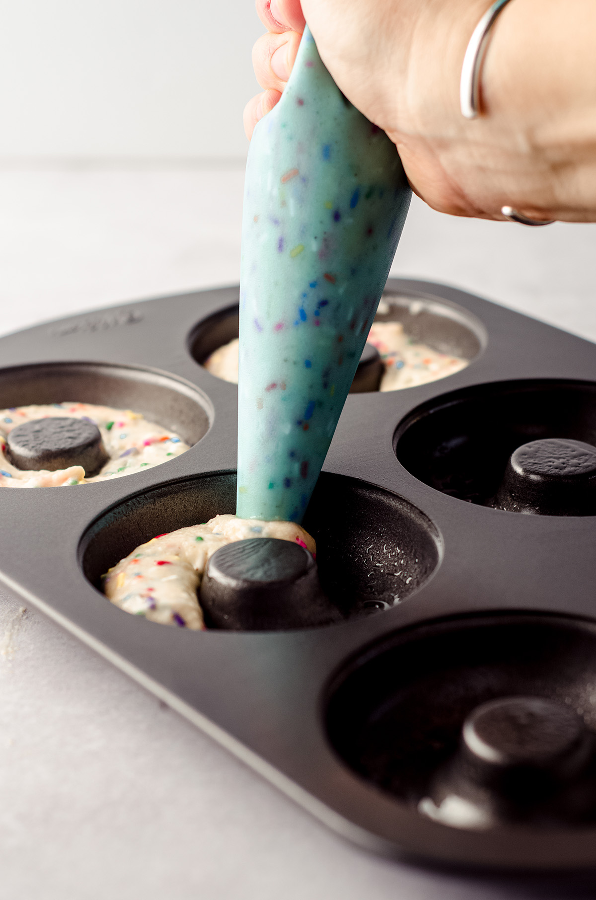 filling a donut pan with funfetti donut batter with a piping bag