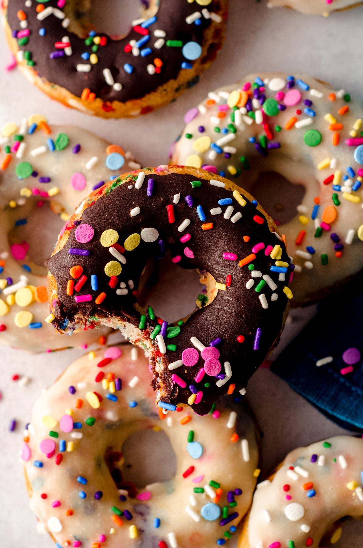 aerial photo of a stack of funfetti donuts and the one on the top has a bite taken out of it