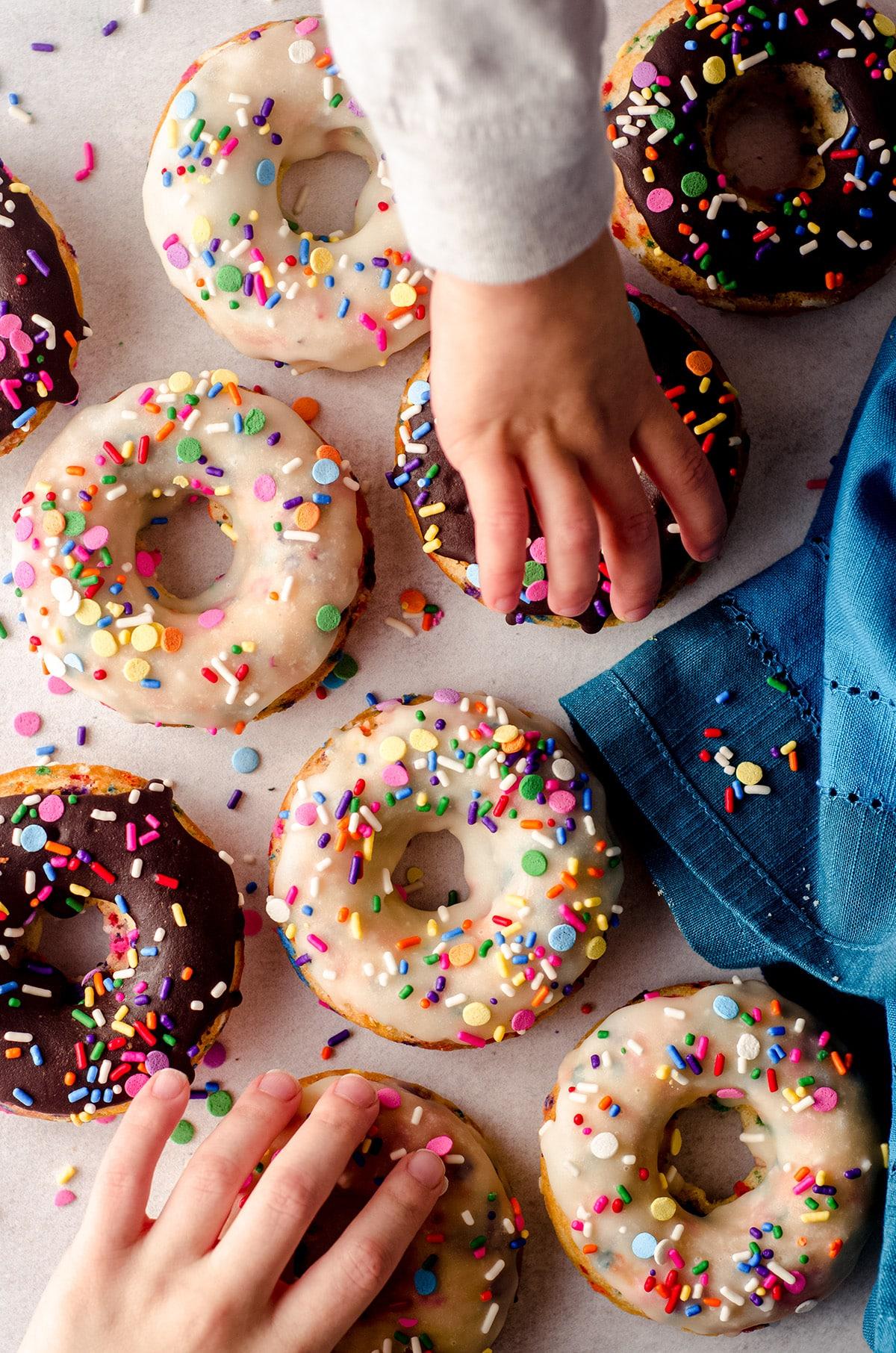 aerial photo of children's hands grabbing funfetti donuts