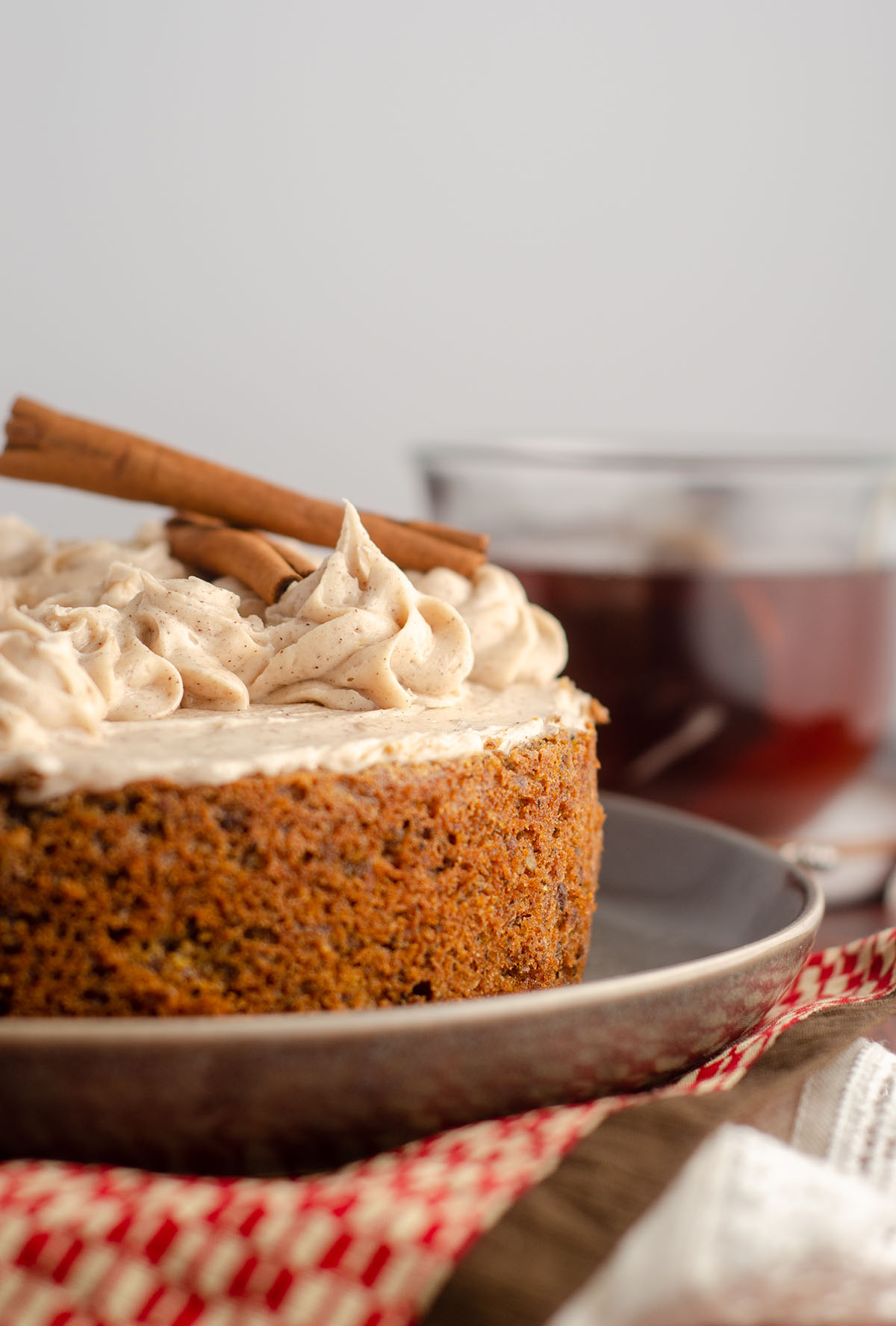 side view of chai cake with cup of chai tea in background