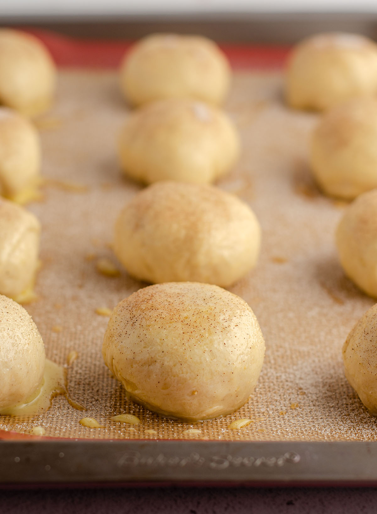 rolls brushed with an egg wash and sprinkled with cardamom-cinnamon-sugar on a baking sheet ready to bake