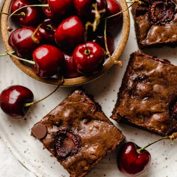aerial photo of cherry brownies on a plate with a bowl of cherries