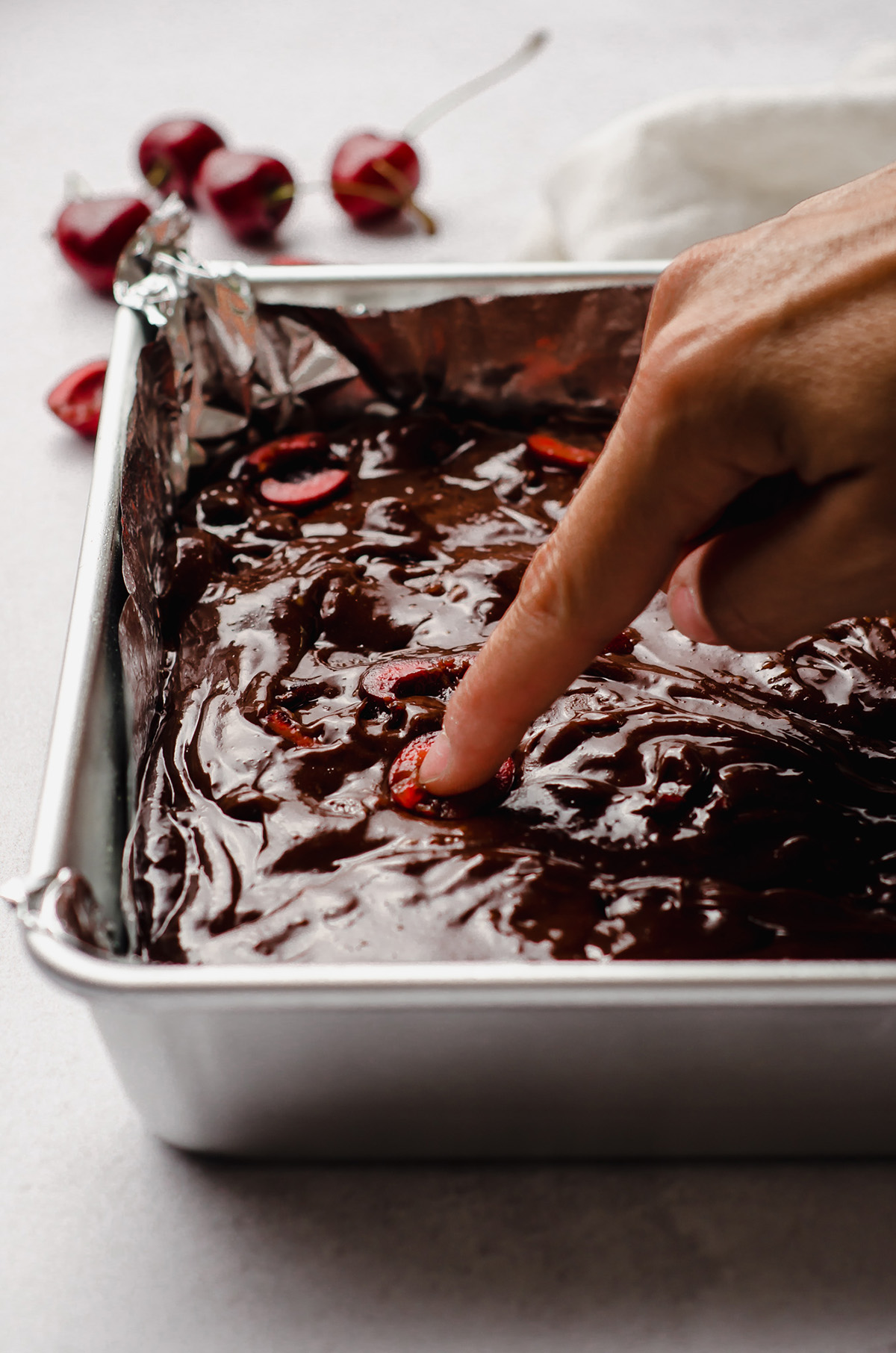 pressing a cherry into cherry brownie batter