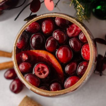 aerial photo of cranberry and orange winter sangria sitting in a glass with a cinnamon sugared rim