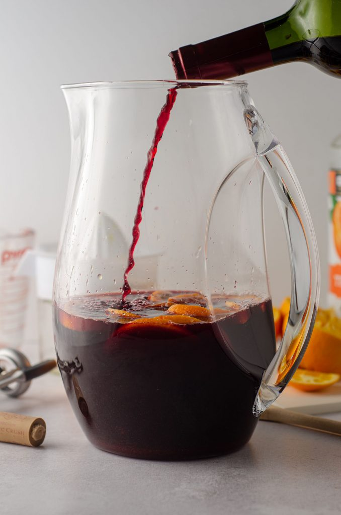 pouring red wine into a pitcher of oranges for sangria