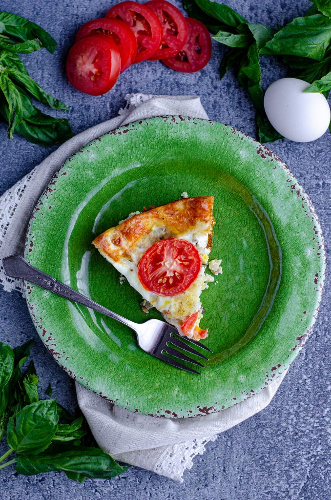 aerial photo of slice of caprese quiche on a green plate with a fork