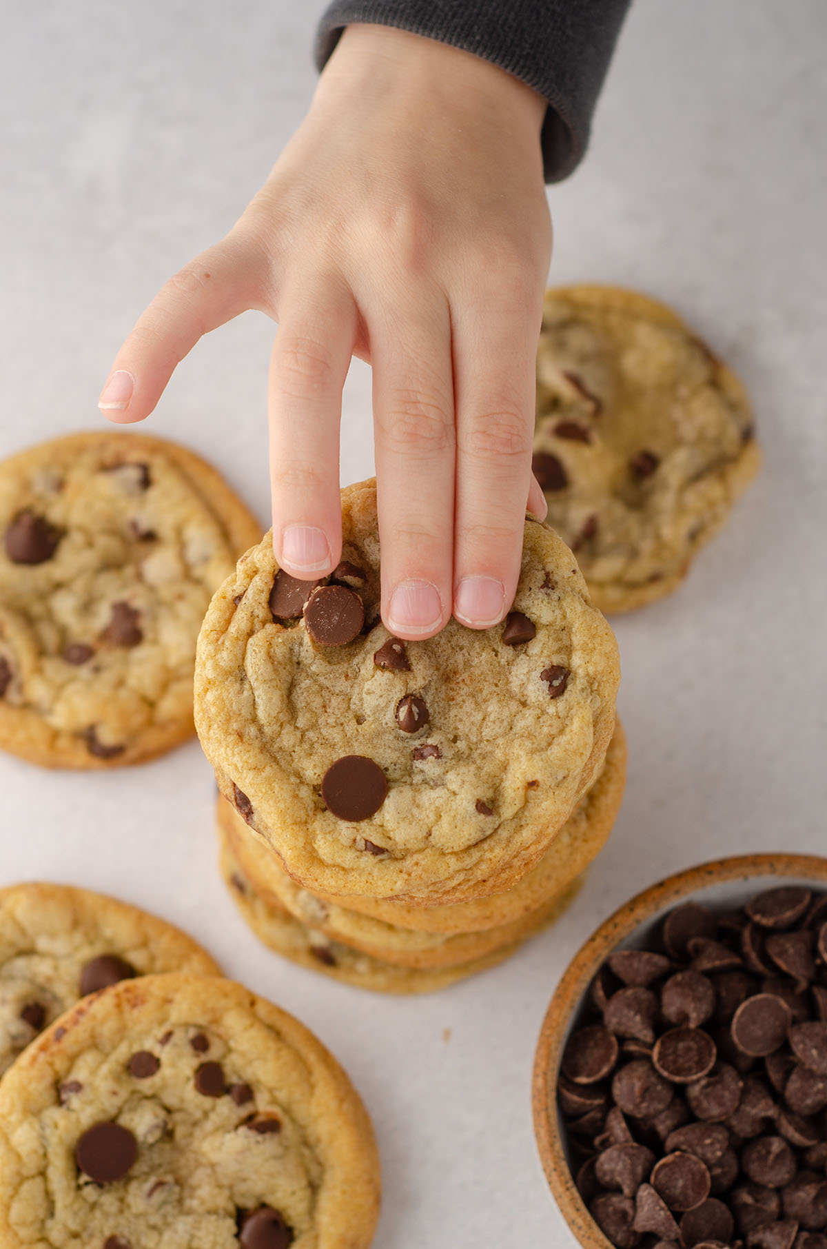 aerial photo of toddler hand reaching to grab a chocolate chip cookies