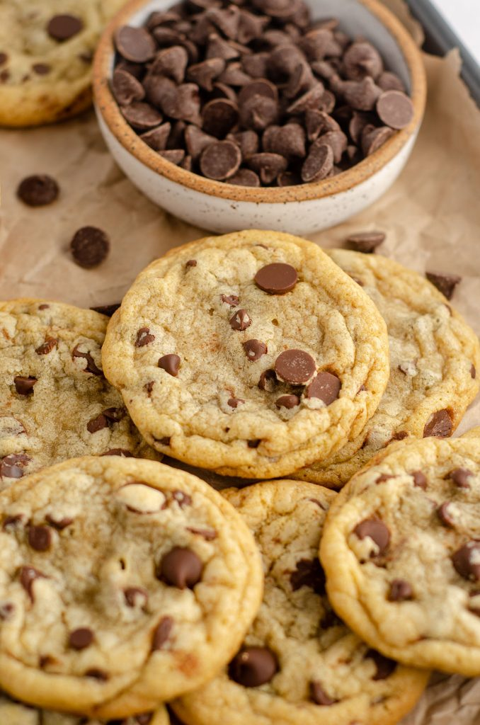 a pile of chocolate chip cookies on a baking sheet lined with parchment paper and a bowl of chocolate chips