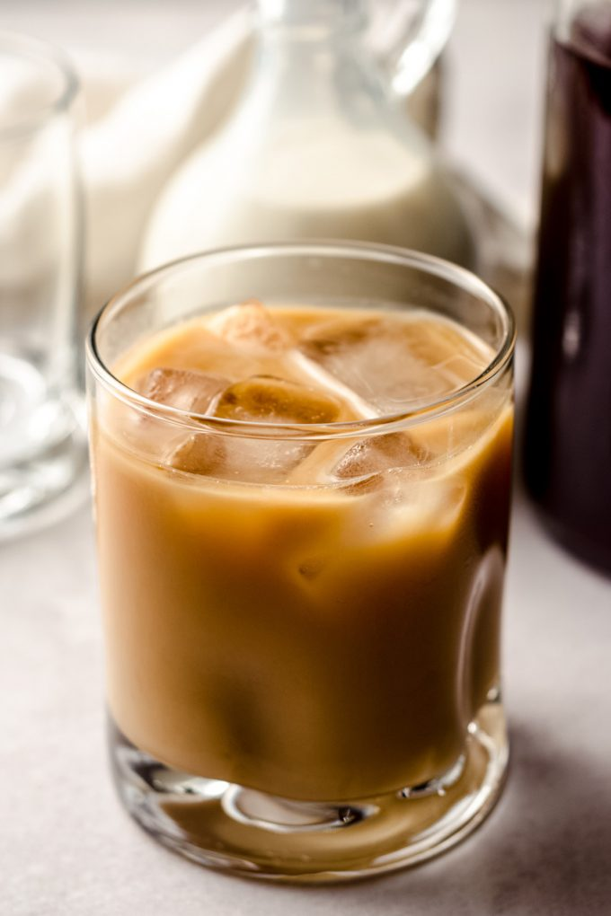 a glass of cold brew coffee with cream and ice cubes