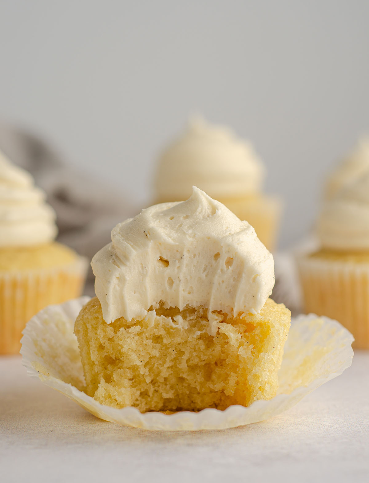 vanilla bean cupcake with vanilla bean buttercream on top sitting in a cupcake liner with a bite taken out of it