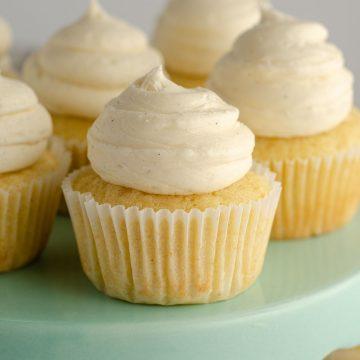 vanilla bean cupcakes sitting on an aqua cake stand