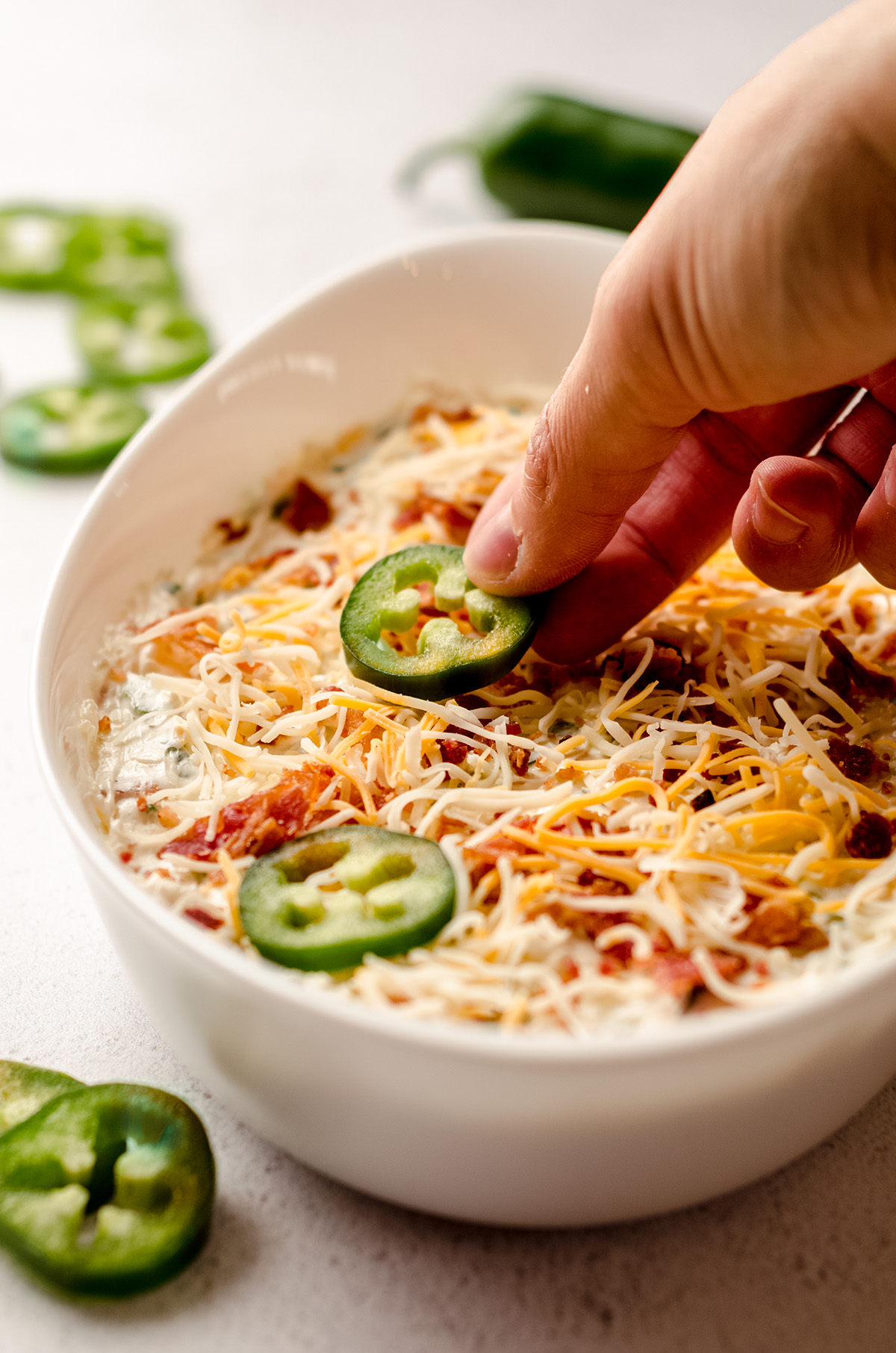 hand placing a slice of jalapeno pepper on top of jalapeno cream cheese dip before baking it