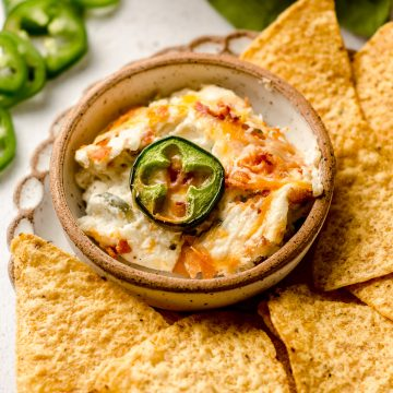 jalapeno cream cheese dip in a bowl on a plate with chips