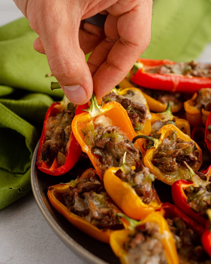 """Mini Philly Cheesesteak Stuffed Peppers: Don't let the """"mini"""" part fool you-- these bite-size peppers are packed with tons of flavor! Recipe includes instructions for four large Philly cheesesteak stuffed peppers."""