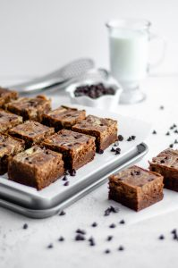 cut brownies on parchment ready to serve with tongs, a glass of milk, and bowl of mini chocolate chips
