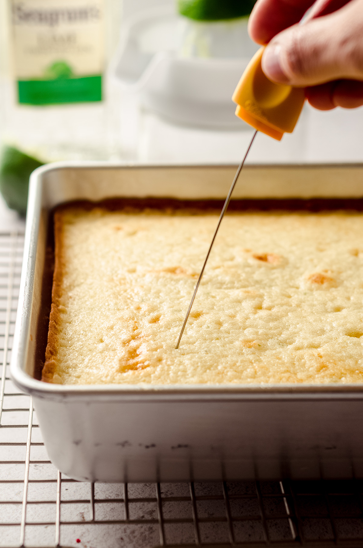 poking holes into a gin and tonic cake