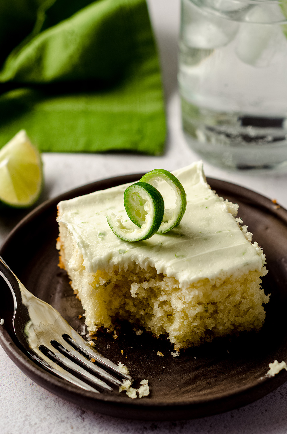 gin and tonic cake on a plate with a fork and a bite taken out of it