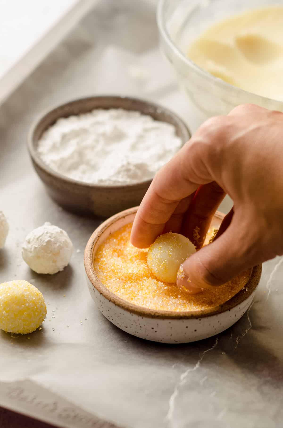 coating a lemon truffle in sprinkles
