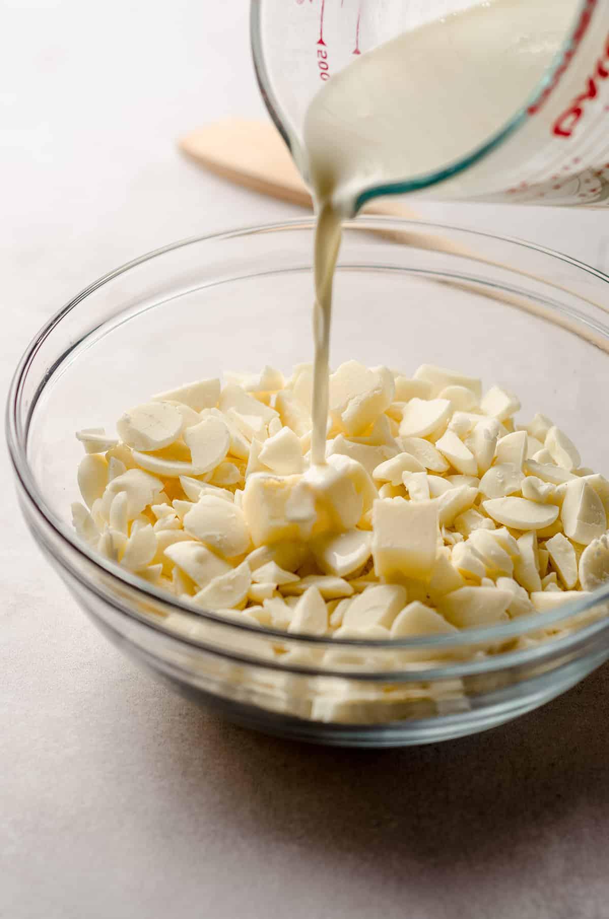 pouring hot cream onto white chocolate to make ganache