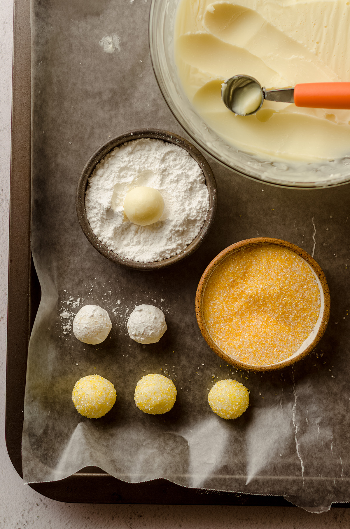 lemon truffles being rolled in powdered sugar