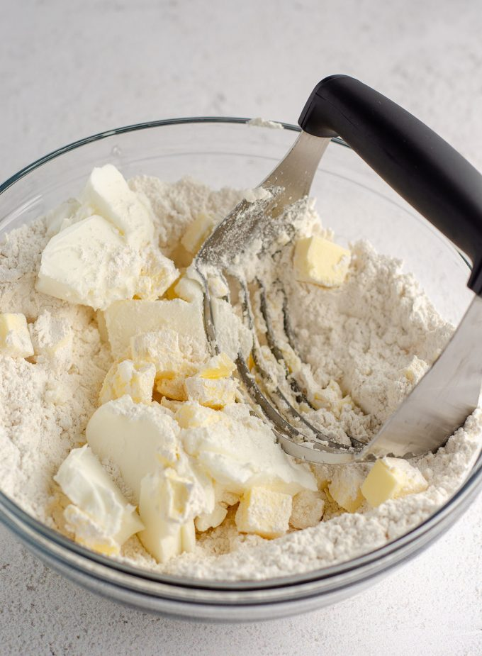 glass bowl with flour mixture, shortening, and butter being cut with a pastry cutter