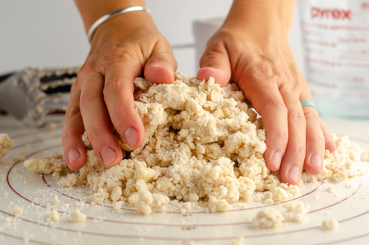 hands shaping crumbly pie dough on a pastry mat