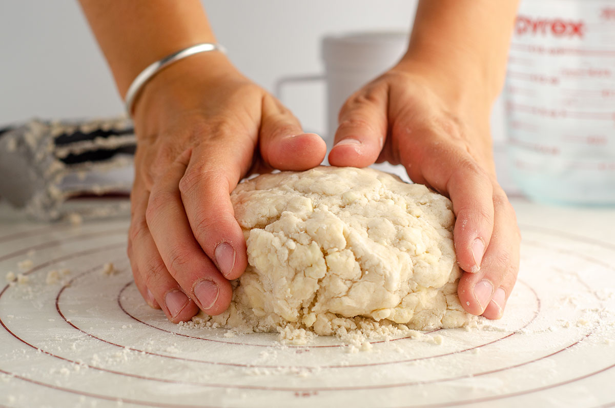 hands shaping pie dough on a pastry mat