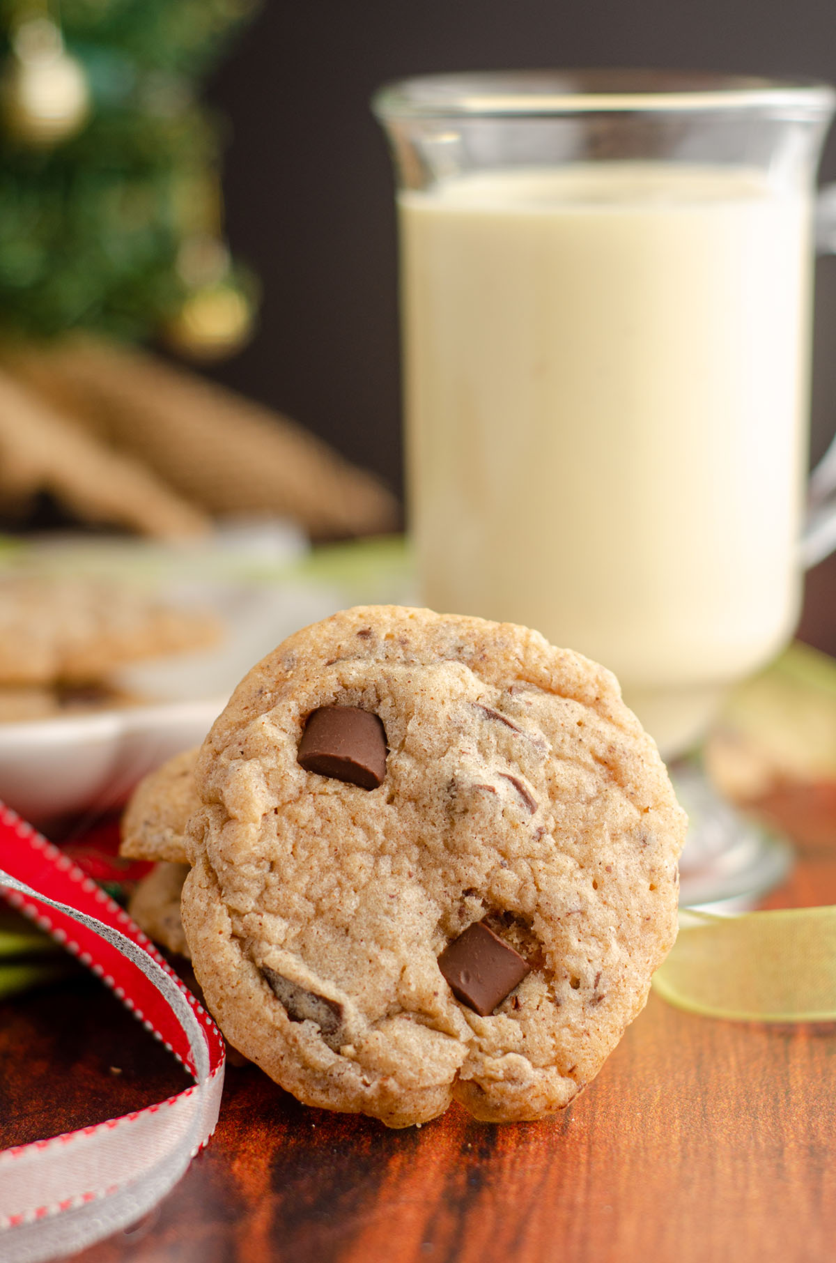 eggnog chocolate chunk cookie sitting with christmas ribbons and eggnog
