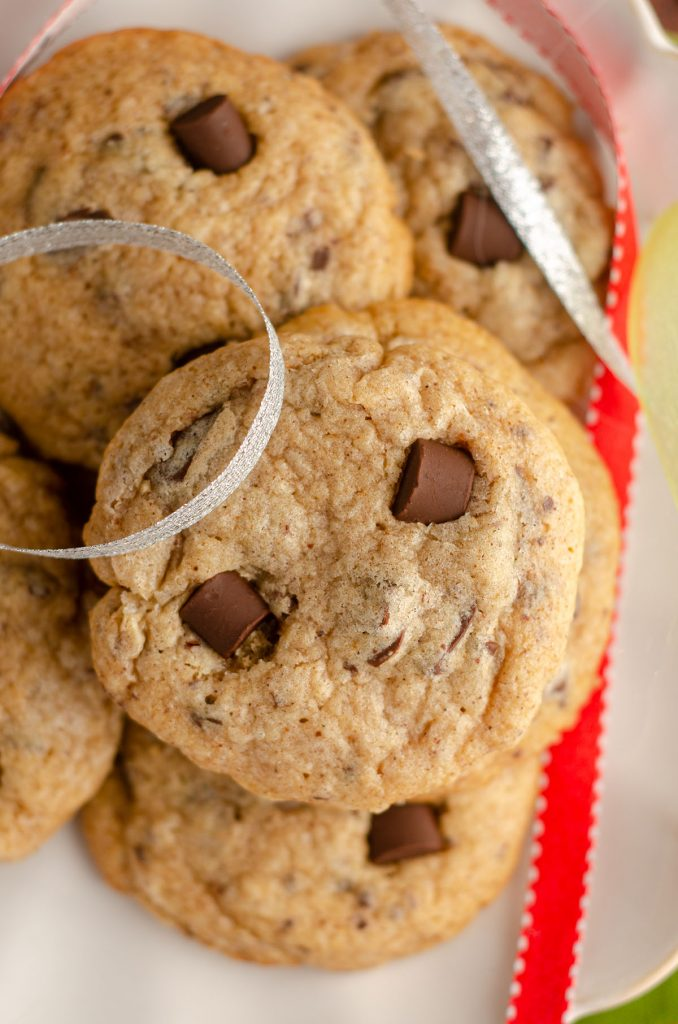 aerial photo of eggnog chocolate chunk cookie on a plate with silver and red ribbons around it