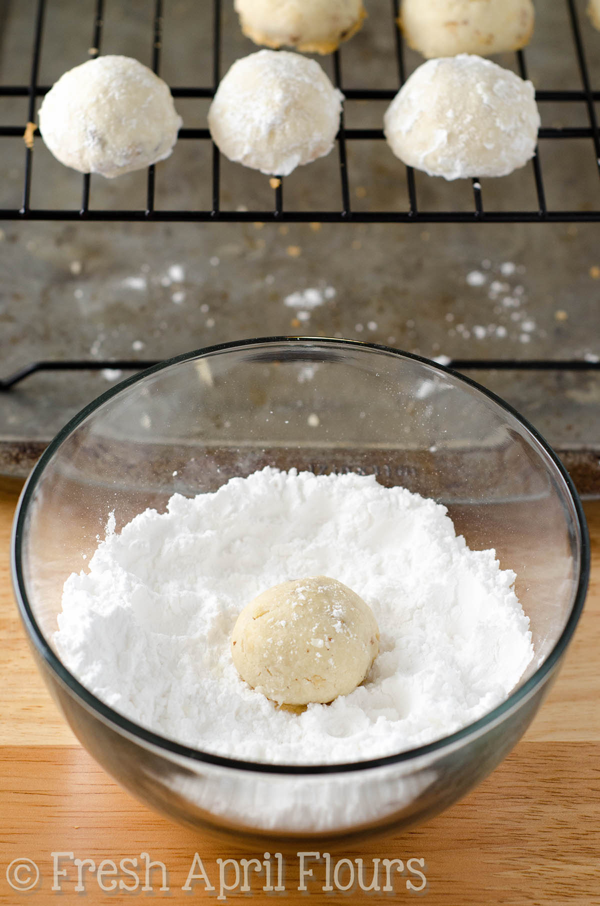 russian tea cakes cookie dough balls getting rolled in powdered sugar