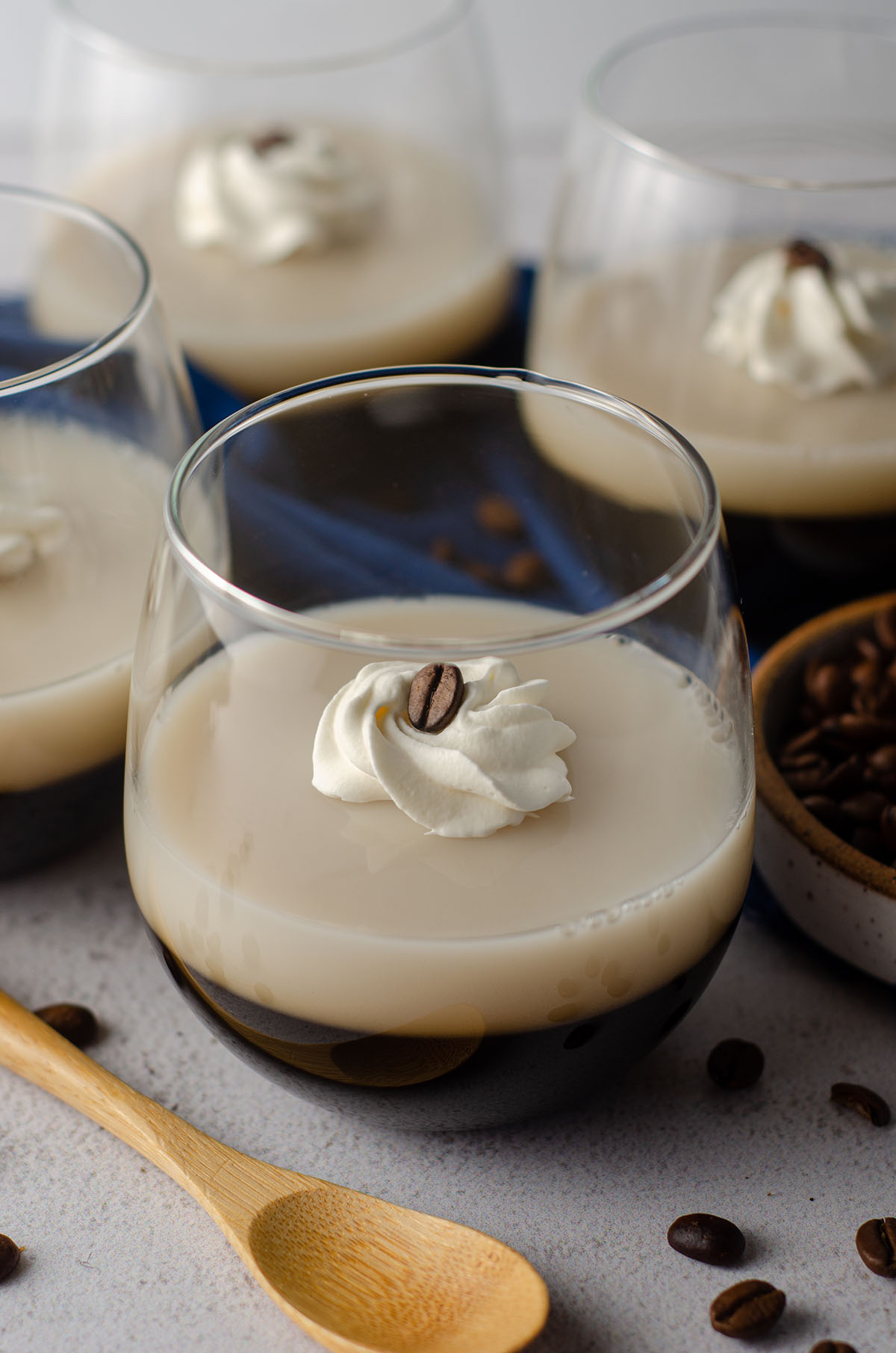 coffee jello in a cup with a dollop of whipped cream and a coffee bean on top