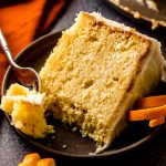 slice of orange creamsicle layer cake on a plate with a fork and a bite taken out of it