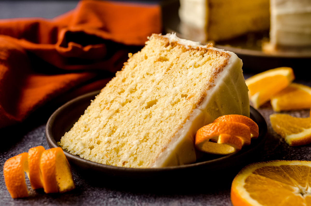 slice of orange creamsicle layer cake on a plate