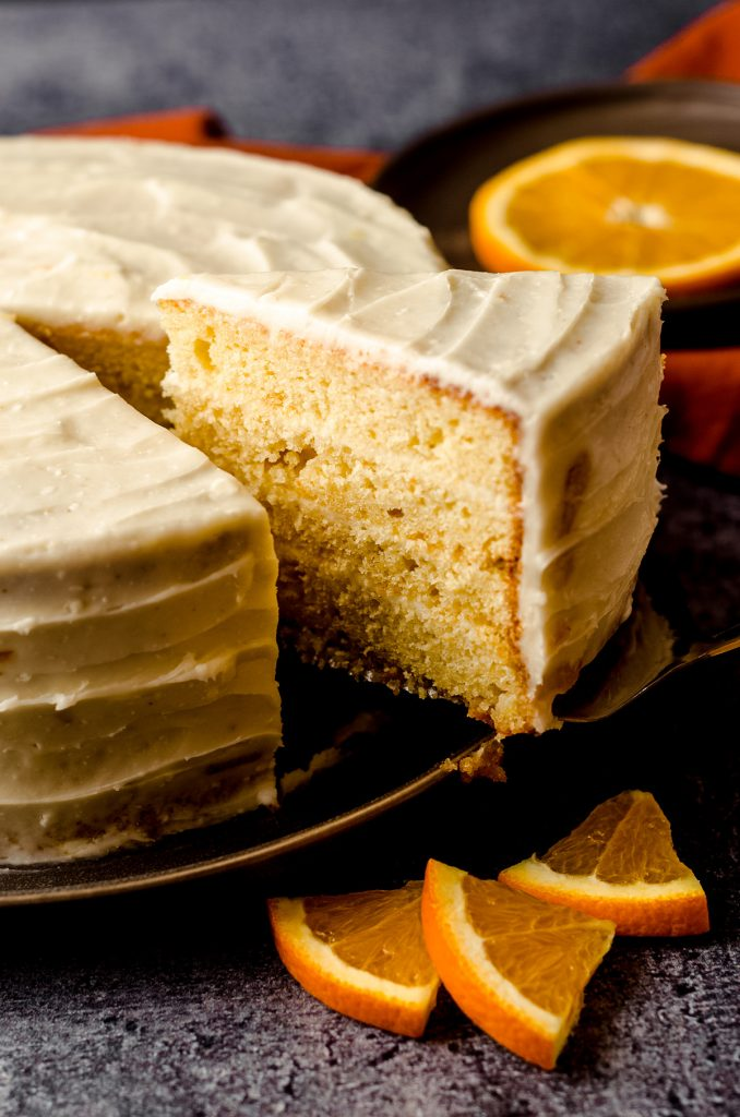 slice of orange creamsicle layer cake being removed to serve