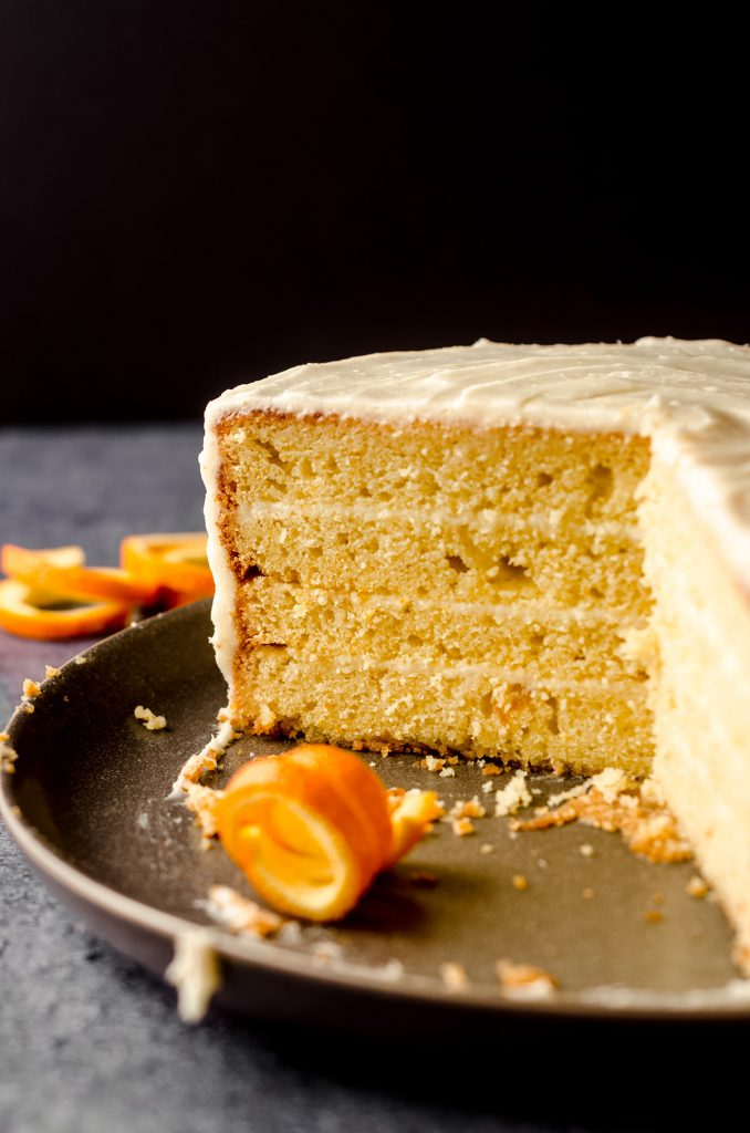 sliced orange creamsicle layer cake on a plate with exposed layers and curled orange peel