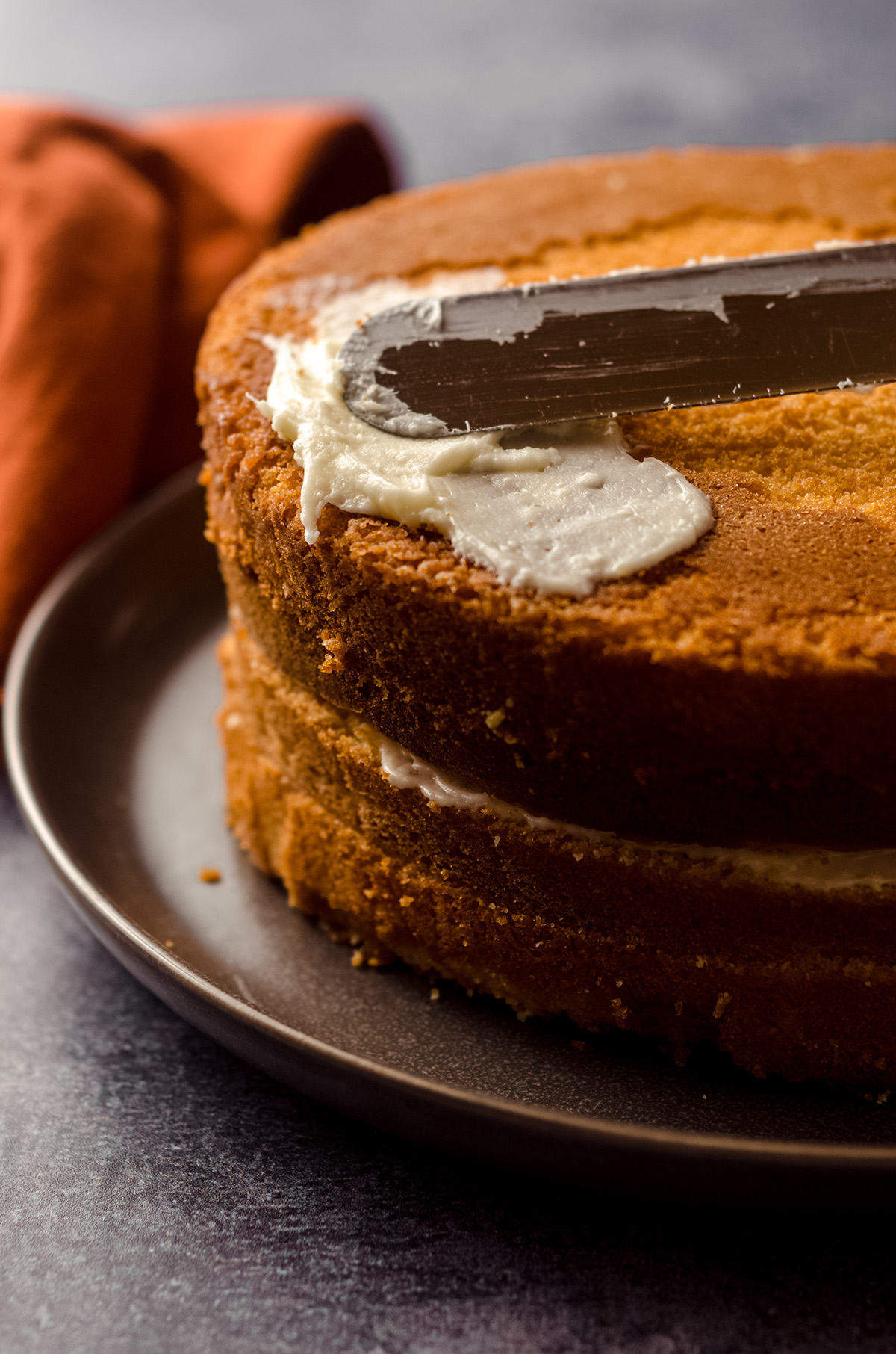 stacked orange creamsicle layer cake being covered in orange cream cheese frosting with a metal spatula