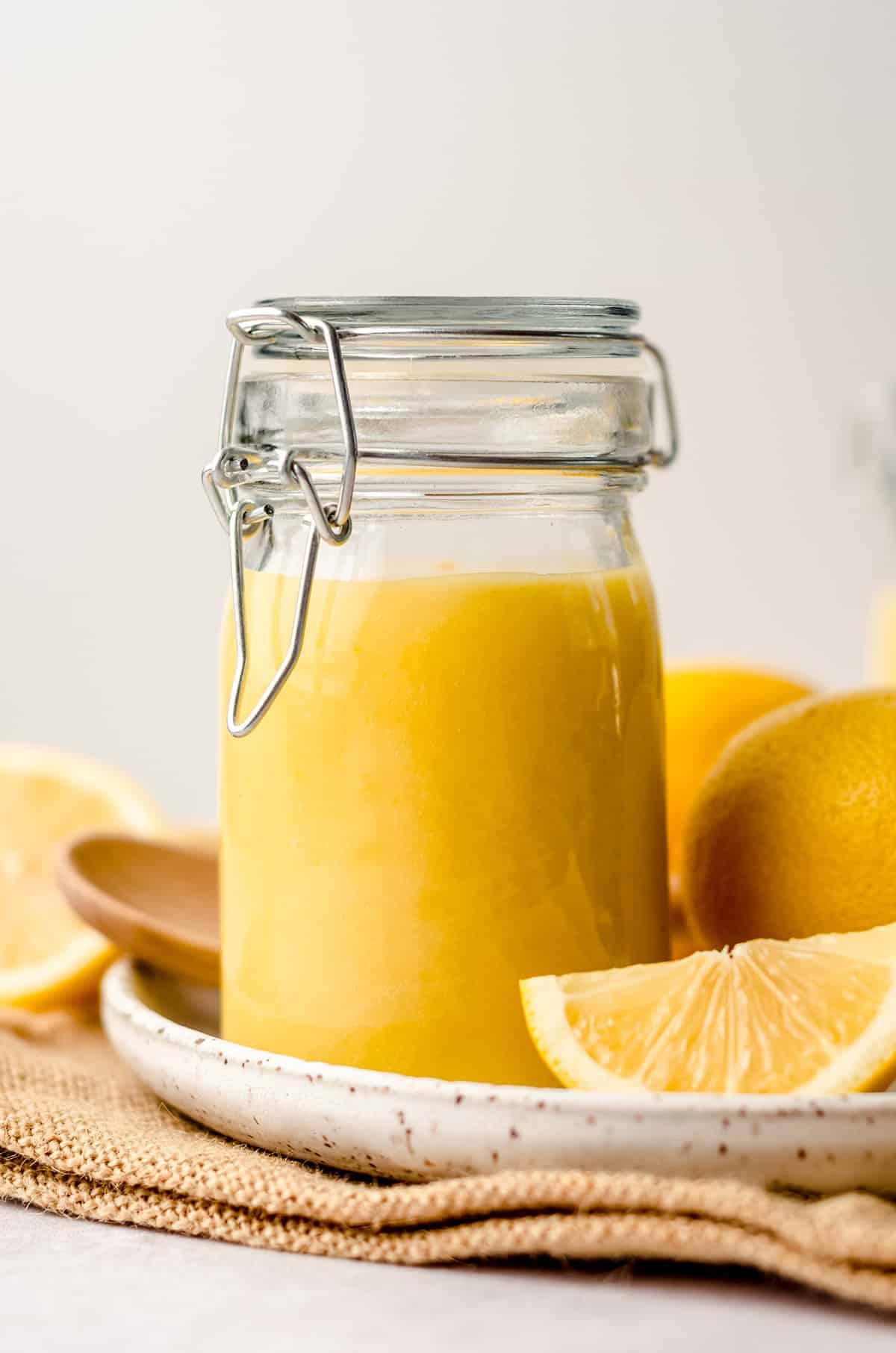 a jar of lemon curd on a plate with lemons