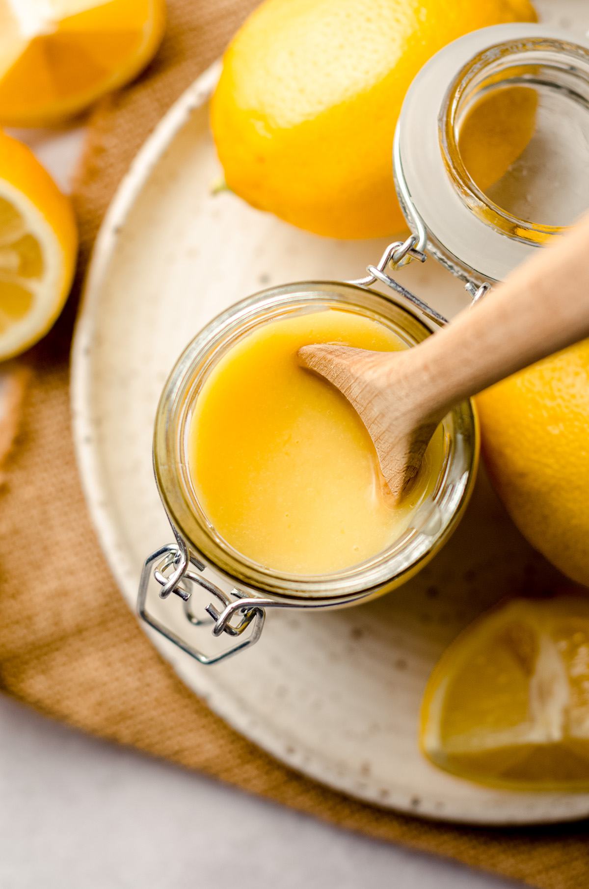 aerial photo of jar of lemon curd with a wooden spoon in it