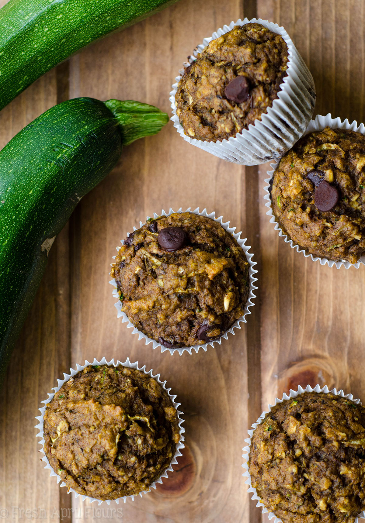 toddler muffins on a surface with zucchini around them
