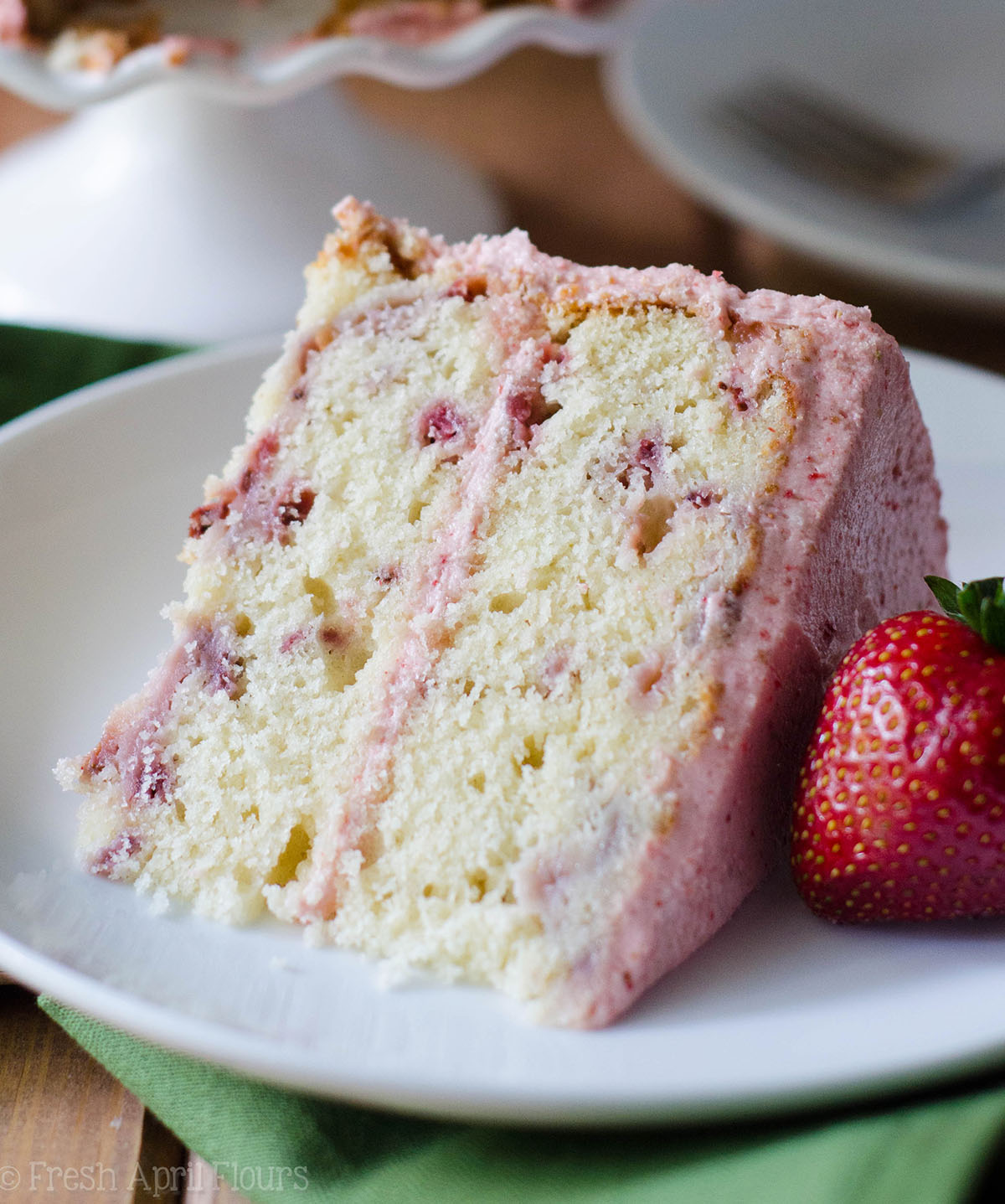 Soft and fluffy homemade strawberry cake made with fresh strawberries and topped with a creamy strawberry buttercream.