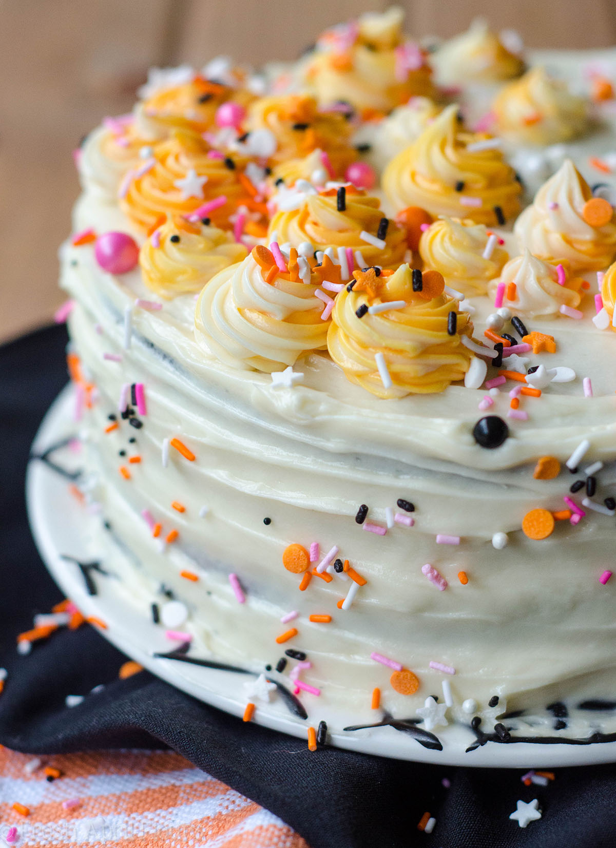 black velvet layer cake decorated with pink and orange sprinkles