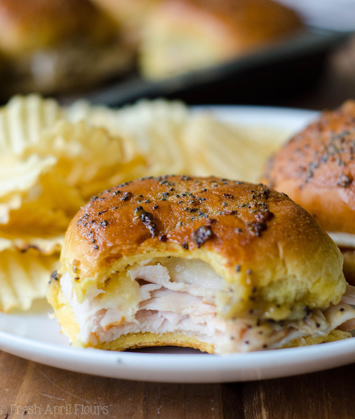 baked turkey and cheese slider sitting on a plate with a bite taken out of it